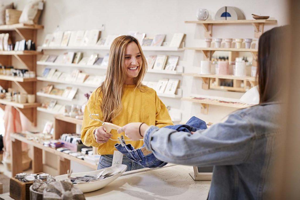 Une vendeuse offrant un cadeau à sa clientèle pour la fidéliser lors d'une animation commerciale.